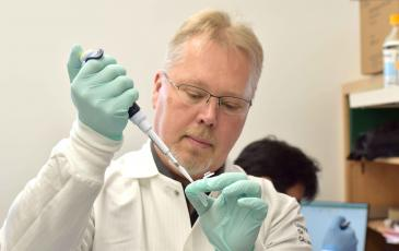 Anders Naar stands in a lab holding a pipette and test tube