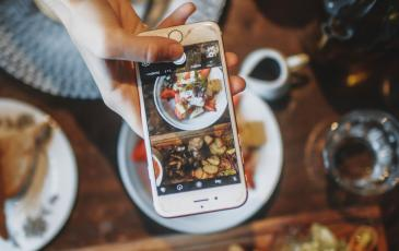Phone taking picture of food on table