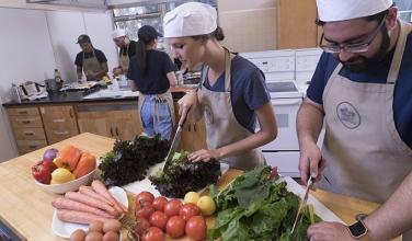 Two students chopping vegetables in a teaching kitchen class